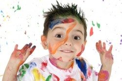 happy little boy covered with different colors of paint