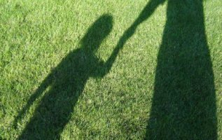 shadows in grass of grown up holding child's hand