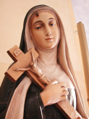 statue of virgin mary holding large crucifix