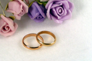 wedding bands next to pink and purple roses